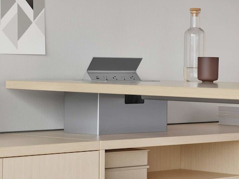 A grey power access unit in the surface of a light wood Canvas Private Office desk. Select to go to the Canvas Private Office specs page.