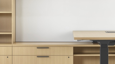 A close-up image of a Canvas Private Office with light wood storage and a height-adjustable desk.