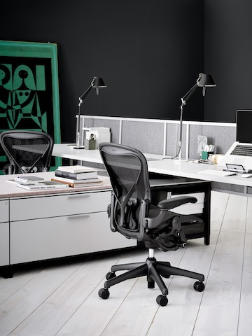 Two Canvas Storage workstations with white storage, white desks, task lighting, and black Aeron office chairs.