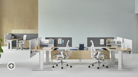 A Canvas Vista workstation with white Mirra 2 office chairs in the foreground and a Canvas Wall workstation with white Mirra 2 office chairs in the background. Select to go to the Individual Workstations page within the Canvas Lookbook.
