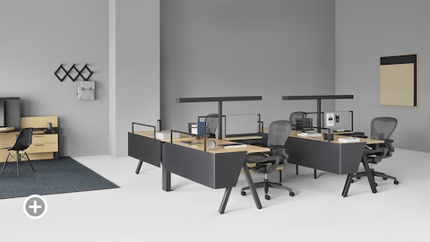 A Canvas Vista workstation with black Aeron office chairs in the foreground and a Canvas Vista collaborative space with display unit in the background. Select to go to the Small Workstations page within the Canvas Lookbook.