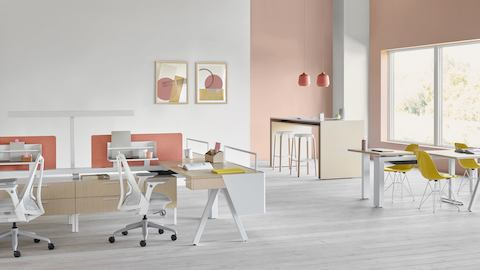 A Canvas Vista workstation in light wood and white with modesty screen, pink fabric screen, and gray Sayl office chairs.