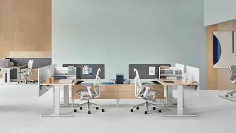 Canvas Vista workstations in light wood and white with gray Mirra 2 office chairs and a conference room with a gray Cosm office chair in the background.