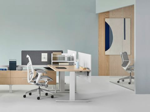 A Canvas Vista workstation with a Mirra 2 office chair and a conference room with a gray Cosm office chair in the background.