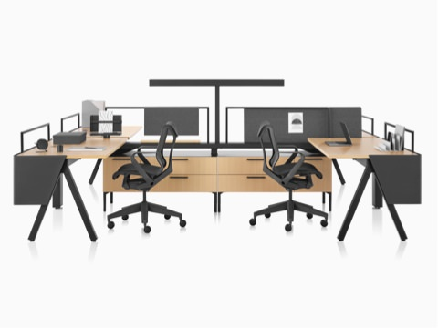 A Canvas Vista workstation in light wood and black with modesty screens, t-shaped lights, and black Cosm office chairs.