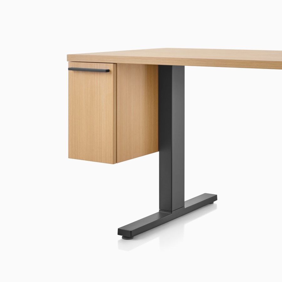 A light wood and black rectangular work surface with suspended cubby drawer and black t-shaped leg.