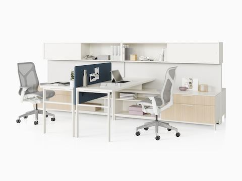 Two grey Canvas Wall workstations with light wood storage, white surfaces, blue screens, and grey Cosm office chairs.