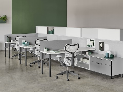 A Canvas Wall workstation with grey screens, upper storage, and white Mirra 2 office chairs.