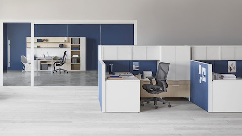 A light wood Canvas Private Office with a dark grey Cosm office chair, and a Canvas Wall workstation.
