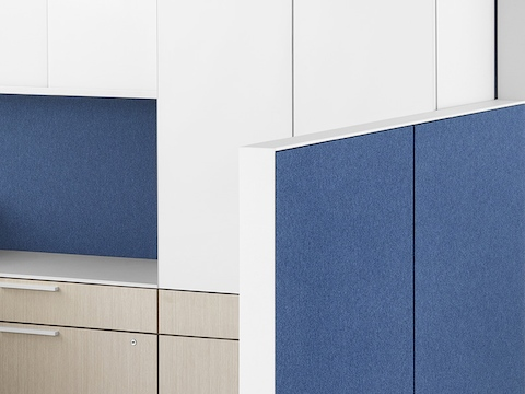 A close-up image of a Canvas Wall workstation with blue panels and white overhead storage. Select to go to the Canvas Wall specs page.