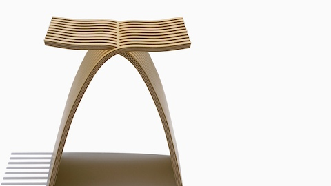 Close front view of a Capelli Stool with a light ash veneer, showing the two pieces of interlocking molded plywood.
