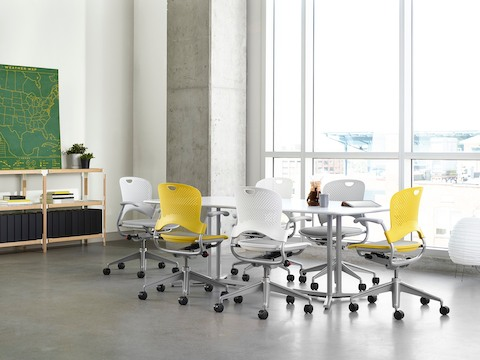 White and yellow Caper Multipurpose Chairs surround a rectangular Everywhere Table in a meeting room.