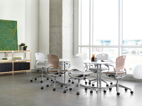 White and light brown Caper Multipurpose Chairs surround a rectangular Everywhere Table in a meeting room.