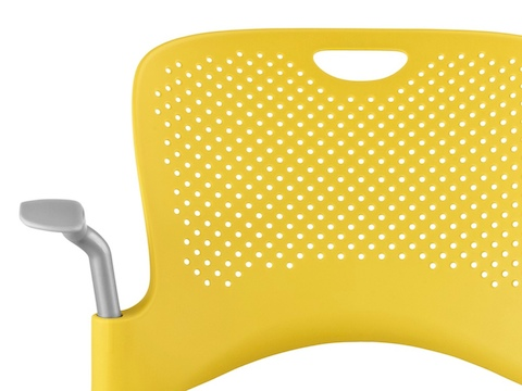 Close view of the perforated back on a yellow Caper Multipurpose Stool.