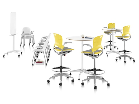 Four yellow Caper Multipurpose Stools with suspension seats around two standing-height round tables.
