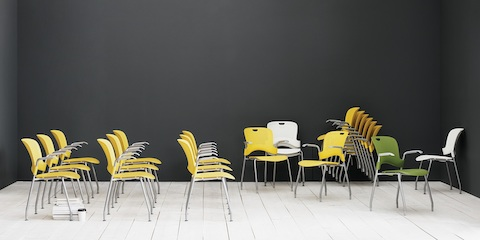 Yellow, green, and white Caper Stacking Chairs in a training environment.