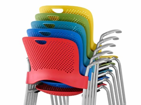 Rear view of red, dark blue, light blue, green, and yellow Caper Stacking Chairs stacked five-high.
