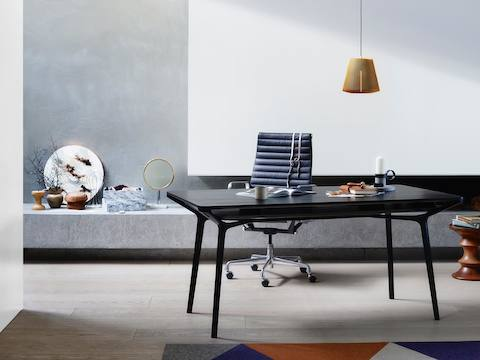 A residential setting featuring a black Carafe Table used as a work desk and paired with a black Eames Aluminum Group Chair.