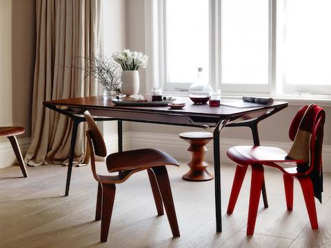 A medium woodgrain Carafe Table used for dining and surrounded by Eames Molded Plywood Chairs and an Eames Walnut Stool.