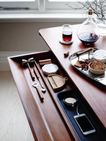 The main drawer of a medium wood Carafe Table, open to reveal a charging smartphone and other items inside.