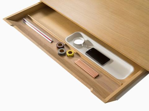 The main drawer of a light wood Carafe Table, open to reveal a ruler, tape, pencils, and smartphone inside.