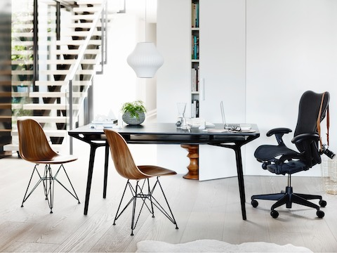 A residential setting featuring a black Carafe Table complemented by a black Mirra 2 office chair and two Eames Moulded Wood Chairs.