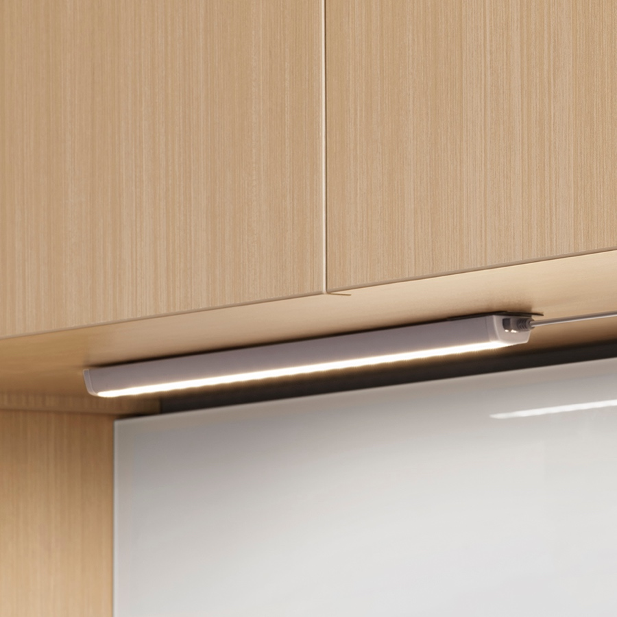 An illuminated Cast LED Light without valance installed underneath a light wood upper cabinet.