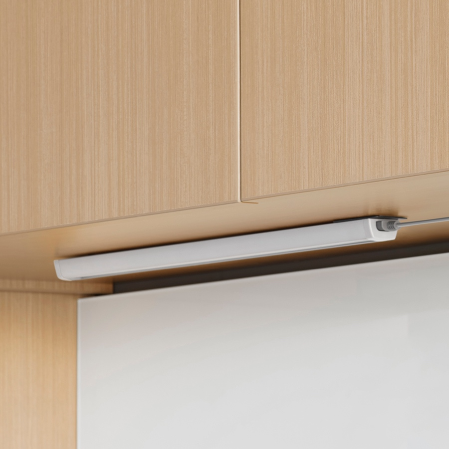 A Cast LED Light without valance installed underneath a light wood upper cabinet.