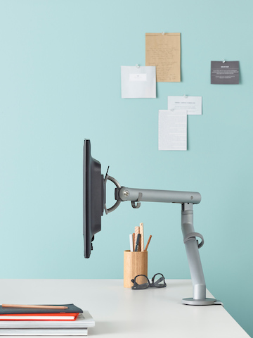 Profile view of a Flo Monitor Arm mounted on a white desk. Select to go to our technology support pages.