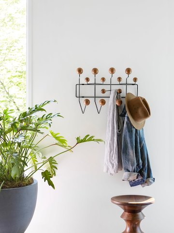 A hat and other clothing articles hang from an Eames Hang-It-All coat rack.