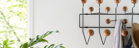 An Eames Hang-It-All coat rack, consisting of solid wood balls and a black wire frame.