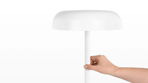 A hand touches the stem of a white Ode Lamp to turn it on or off. Select to go to our lighting pages.