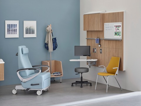 A patient recliner, side chair and stool in an exam room.