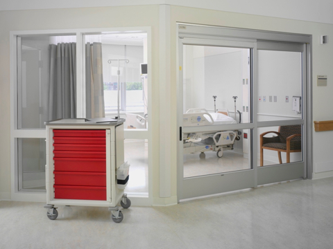 A mobile healthcare storage cart with casters and red drawers positioned outside a glass-walled patient room.