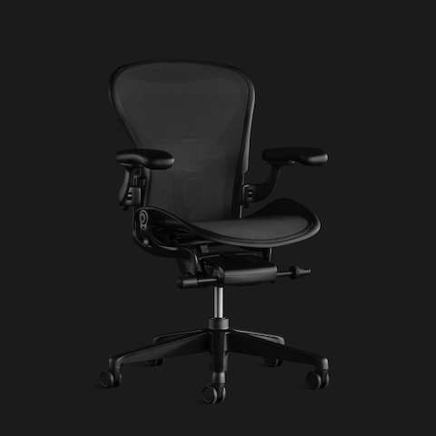 An Aeron Chair in all black against a black background, shown from the front at a slight angle.