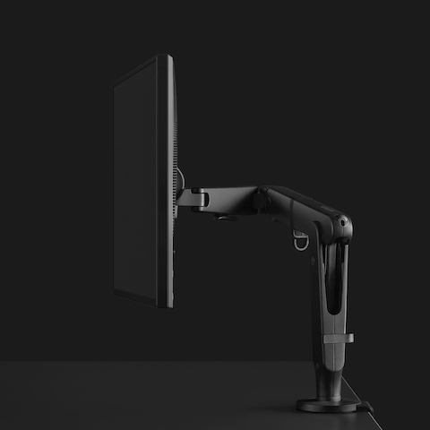 Dark grey Ollin Monitor Arm shown from the side with a dramatically lit black background.