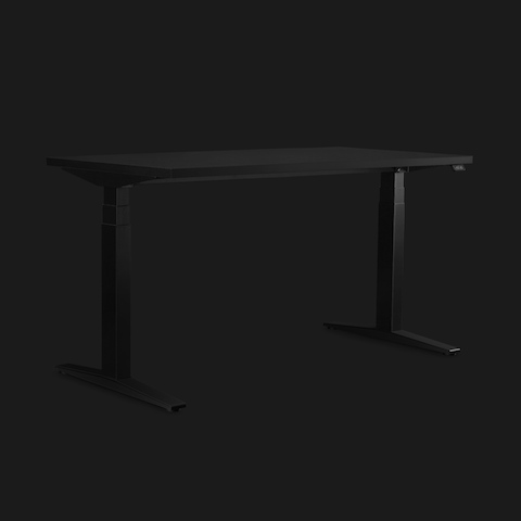 Dark grey height-adjustable Ratio Gaming Desk shown on an angle with a dramatically lit black background.