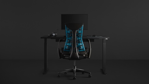 A full gaming setup with an Embody Gaming Chair pulled up to the Motia Gaming Desk with an Ollin Monitor Arm on top of it, all on a black background.
