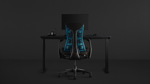 A full gaming setup with an Embody Gaming Chair pulled up to the Nevi Gaming Desk with an Ollin Monitor Arm on top of it, all on a black background.