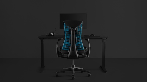 A full gaming set-up with an Embody Gaming Chair pulled up to the Ratio Gaming Desk with an Ollin Monitor Arm on top of it, all on a black background.