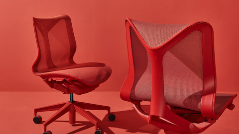 Two armless low-back Cosm Chairs in Canyon red on a red background. Select to go to the Cosm Chairs product page.