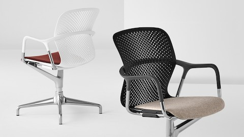 A white Keyn side chair shown from a three-quarter back view and a black Keyn side chair shown from a three-quarter front view.