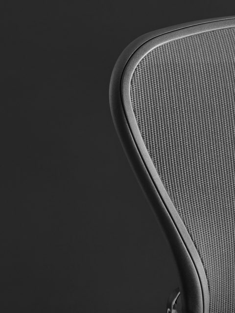 Close-up of the mesh back on a black Aeron office chair.