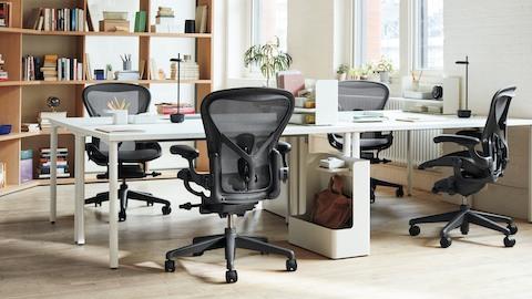An open-plan office with four desks arranged together two-by-two, each with an Aeron Chair pulled in.