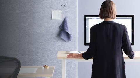 A woman, seen from behind, views a computer monitor while standing at a height-adjustable desk.