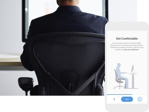A back-view photo of a person sitting in an Aeron Chair and facing a monitor. The photo is overlaid with a image of the wellness app.