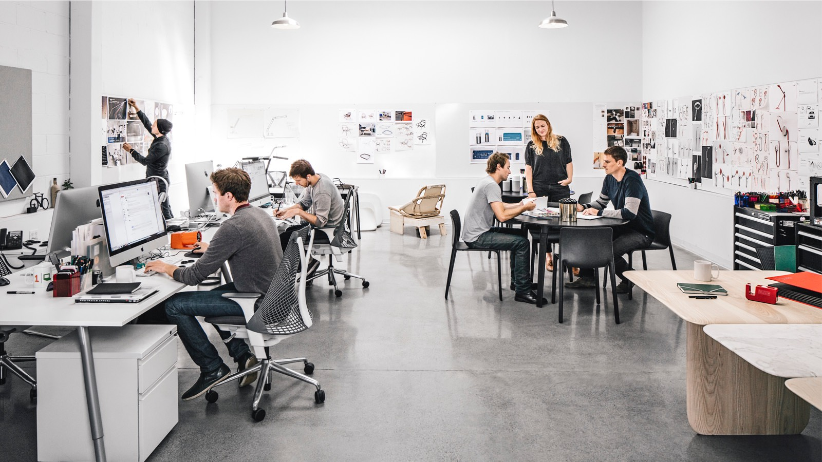 A photo of a workplace with people working at computers while sitting at long desks in Aeron Chairs. A trio of colleagues meet nearby.