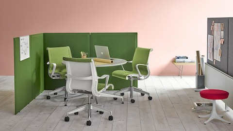 Green screens define a partially enclosed meeting area that contains a round table and green Setu office chairs.