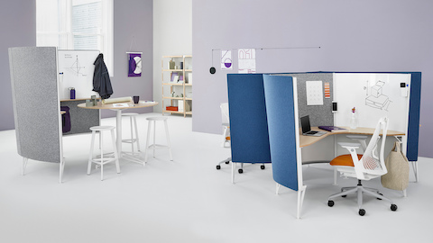 A Prospect collaborative space near two Prospect solo spaces with blue acoustic fabric and white Sayl Chairs with orange upholstered seats.