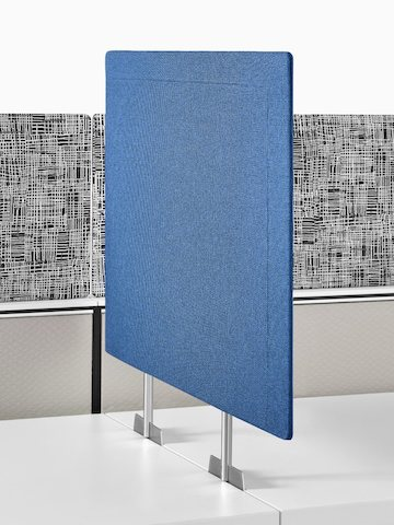 A blue privacy screen inserted between two adjacent work surfaces.